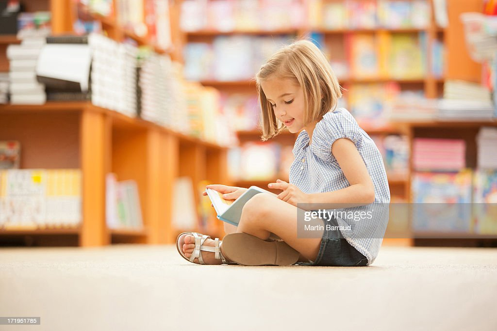 Niña sentada en el piso de biblioteca con libro : Foto de stock