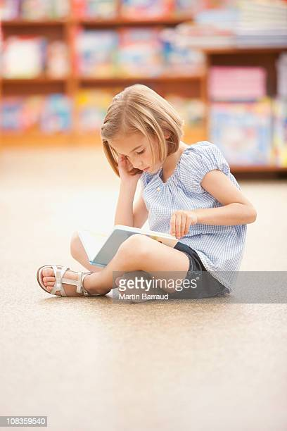 Girl sitting on floor reading book