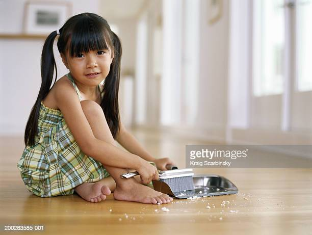 Girl (4-6) sitting on floor sweeping up crumbs into dust pan, portrait
