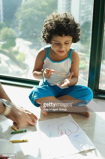 Girl sitting on floor with crayons and paper, fathers hands in foreground