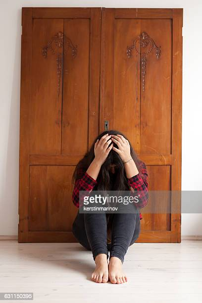 Girl sitting on floor with her  head in her hands