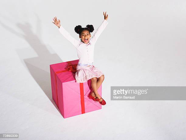 Girl (6-7) sitting on giant present, arms raised, portrait