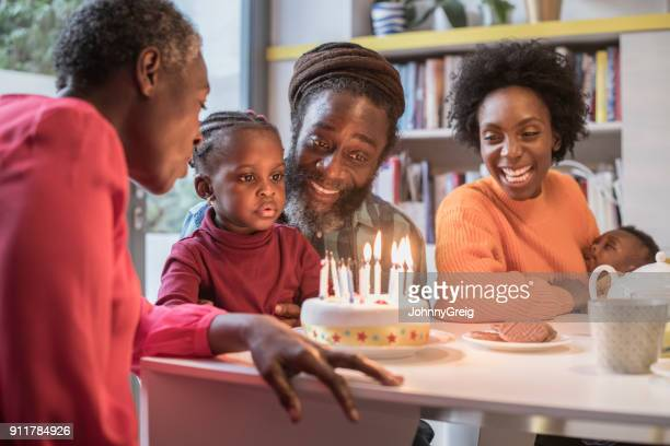 Girl sitting on grandfather's lap with birthday cake on table