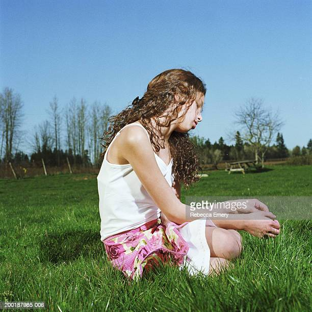 girl (9-11) sitting on grass, side view - emery stock photos and pictures