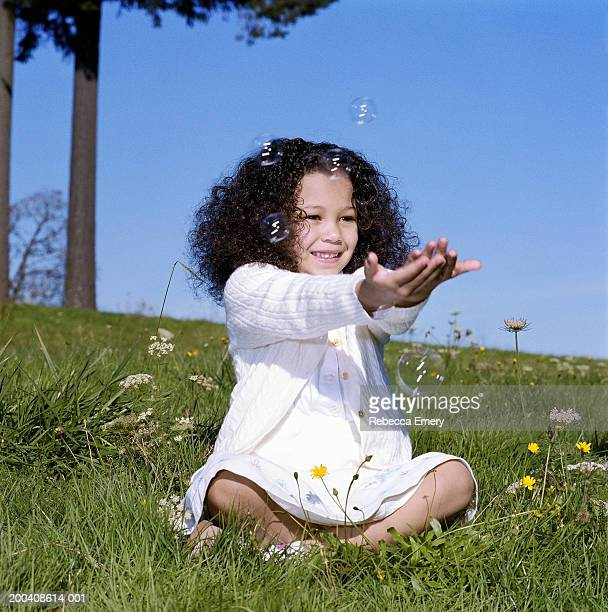 girl (4-6) sitting on grassy hillside, catching bubbles and smiling - emery stock photos and pictures