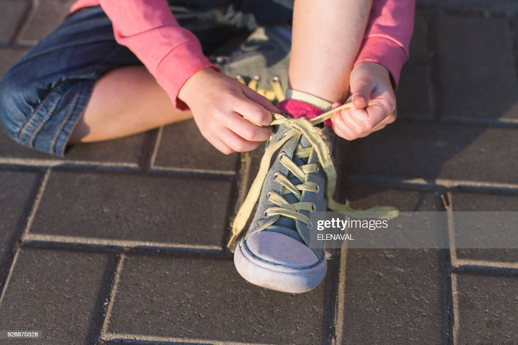 Girl sitting on ground tying her shoelaces : Stock Photo