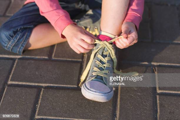 girl sitting on ground tying her shoelaces - tie stock pictures, royalty-free photos & images