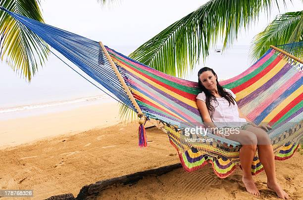 Girl sitting on hammock by the beach w/ palm trees