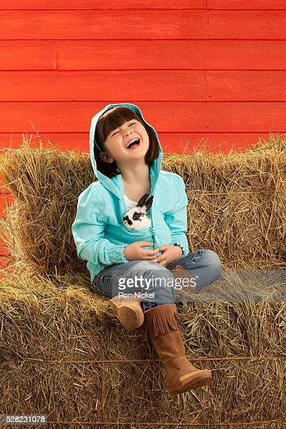 A girl sitting on hay bales holding a bunny rabbit