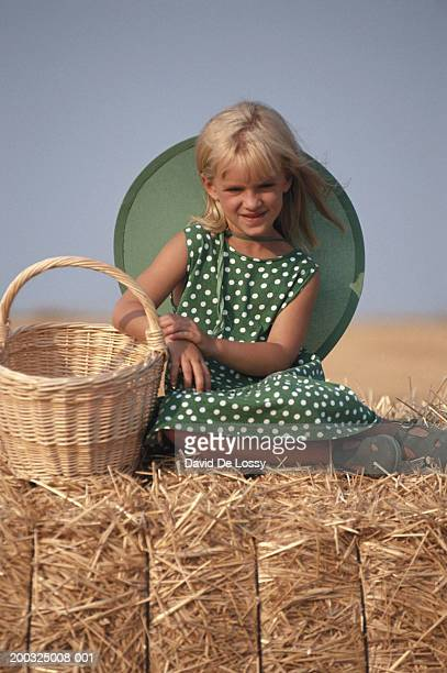 Girl (6-7) sitting on haystack