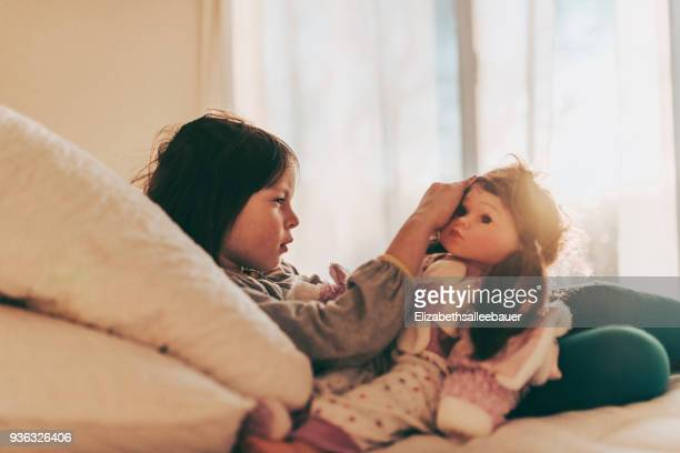 Girl sitting on her bed playing with a doll