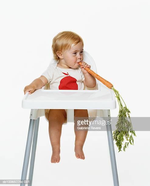 Girl (21-24 months) sitting on highchair eating carrot