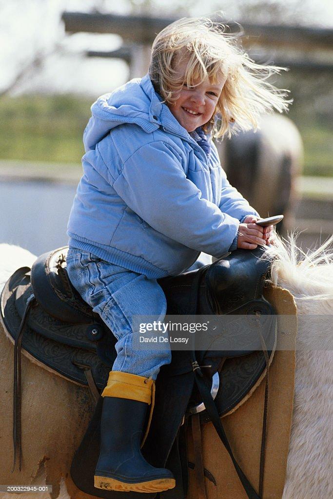 Girl (4-5) sitting on horse back, smiling : Stock Photo