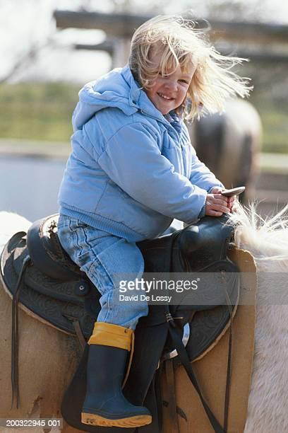 girl (4-5) sitting on horse back, smiling - girl blowing horse - fotografias e filmes do acervo