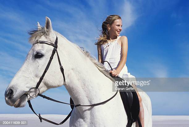 Girl (11-13) sitting on horse on beach, smiling