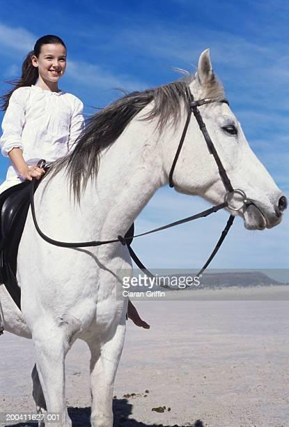 girl (9-10) sitting on horse on beach, smiling, portrait - caballo blanco fotografías e imágenes de stock