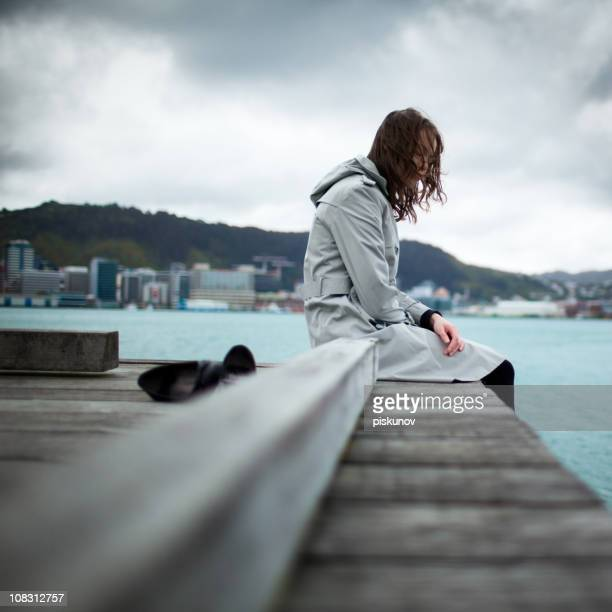Girl sitting on jetty along