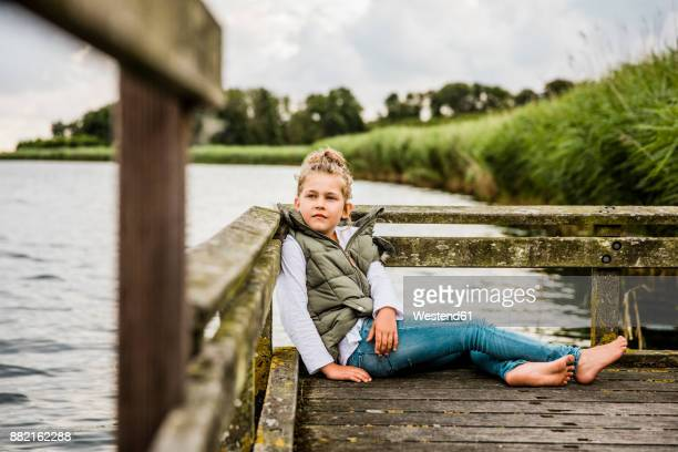 Girl sitting on jetty at a lake