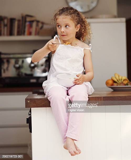 Girl (4-6) sitting on kitchen counter eating cereal, looking to side