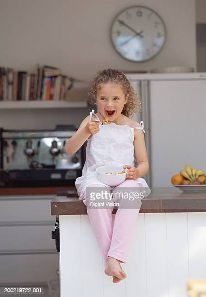 Girl (4-6) sitting on kitchen counter eating cereal, smiling