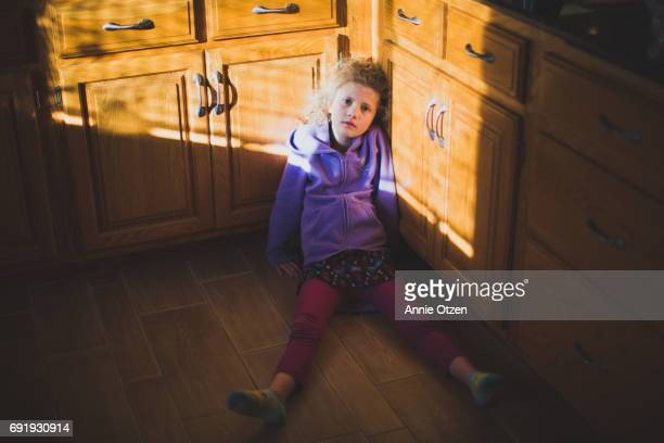 Girl Sitting on Kitchen Floor