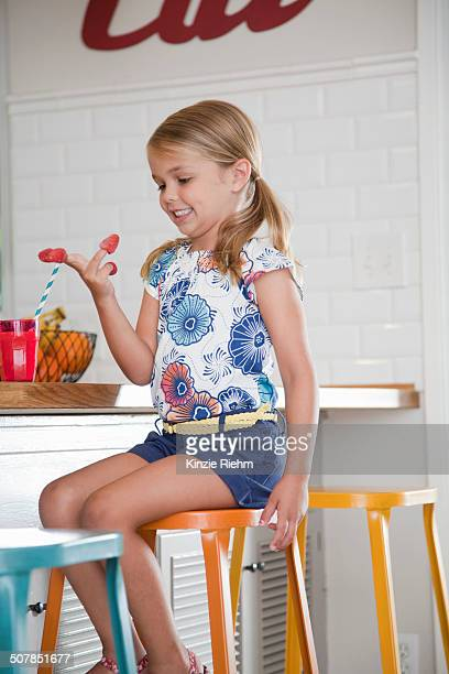 Girl sitting on kitchen stool with raspberries on her fingers