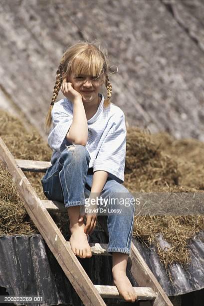 girl (6-7) sitting on ladder by roof - calça comprida - fotografias e filmes do acervo