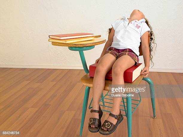 girl sitting on large book in school desk - mini skirt stock photos and pictures