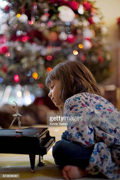 Girl sitting on living room floor listening to toy piano music box at Xmas