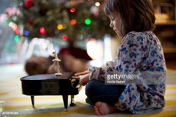 Girl sitting on living room floor playing toy piano music box at Xmas