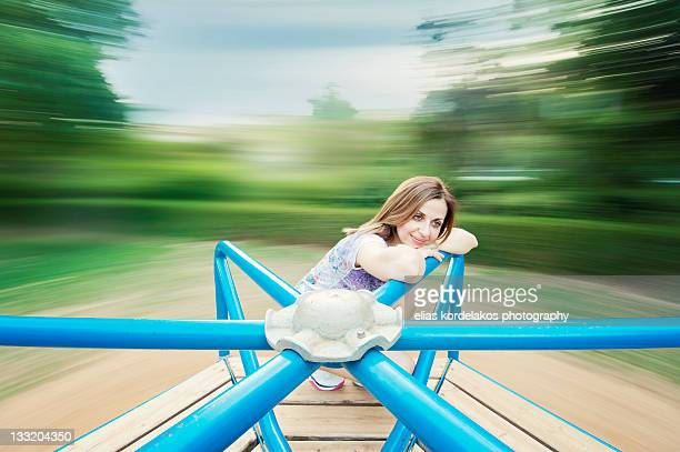 Girl sitting on merry go round