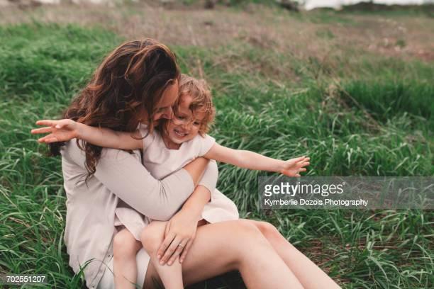 Girl sitting on mothers lap on windy field
