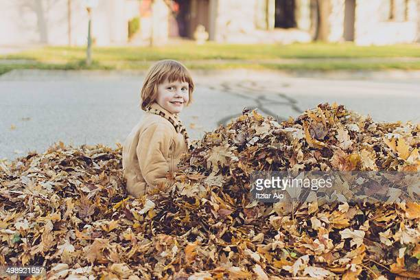 girl sitting on mountain of autumn leaves