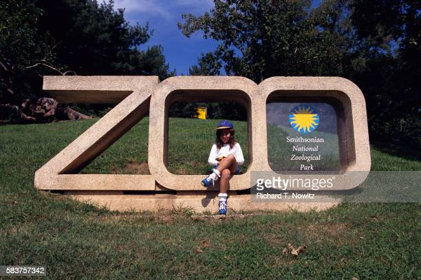 Girl Sitting on National Zoo Sign