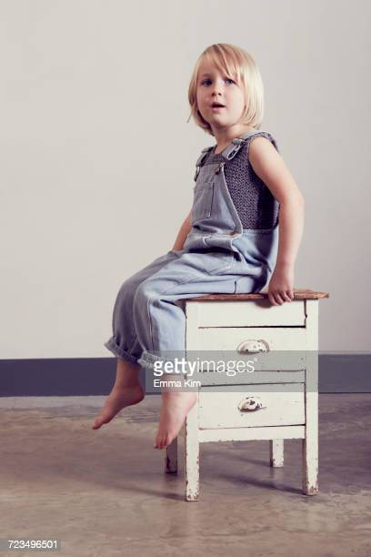 girl sitting on old cabinet looking away - emma white stockfoto's en -beelden