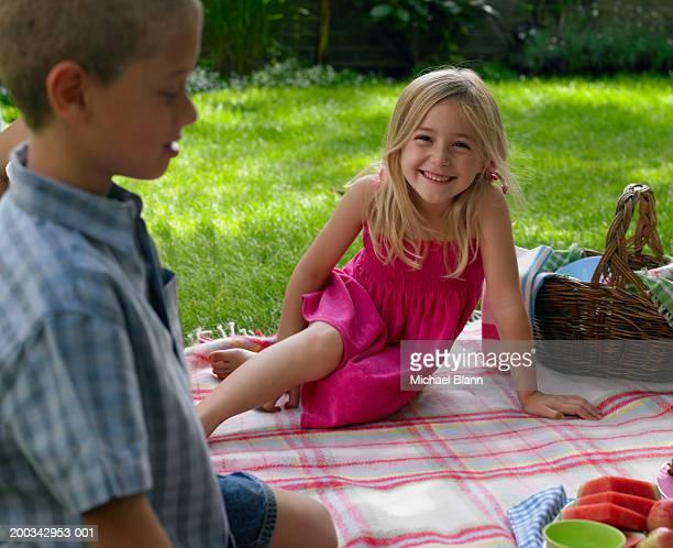 Girl (6-8) sitting on picnic blanket in garden, smiling, portrait