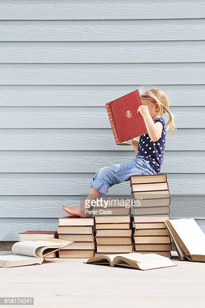 girl sitting on pile of books .Girl reading book