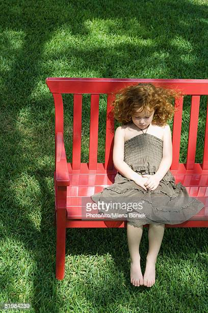 Girl sitting on red bench, high angle view