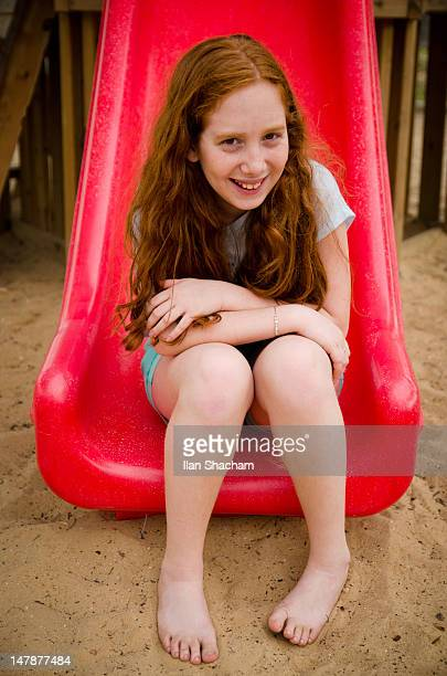 girl sitting on red slide - barefoot redhead stock photos and pictures