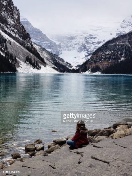 girl sitting on rock by lake against snowcapped mountain - sibley stock photos and pictures