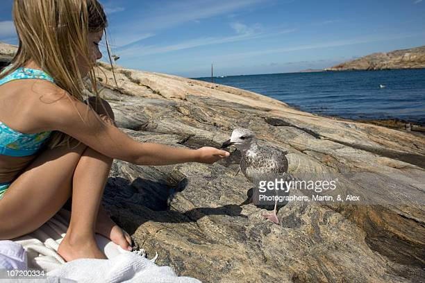 Girl sitting on rock feeding bird