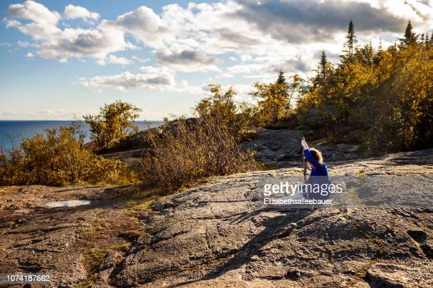 girl sitting on rocks holding a stick, lake superior provincial park, united states - lake superior provincial park stock pictures, royalty-free photos & images