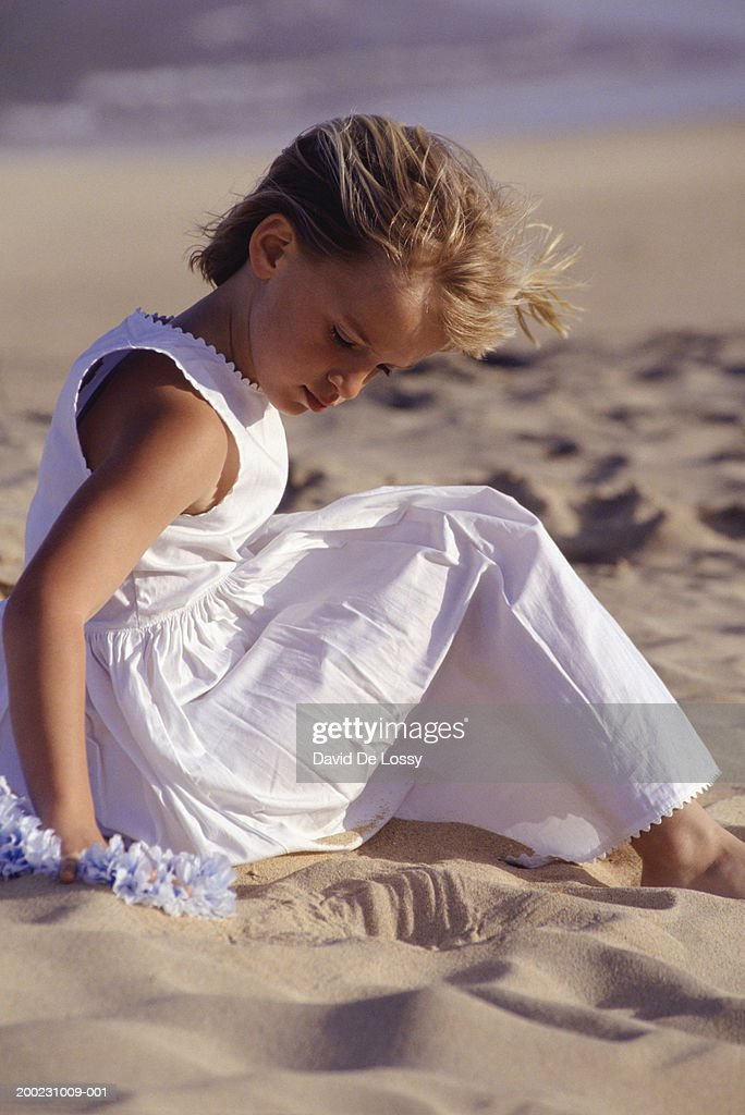 Beautiful Young Woman Sitting Alone On Sand At The Beach