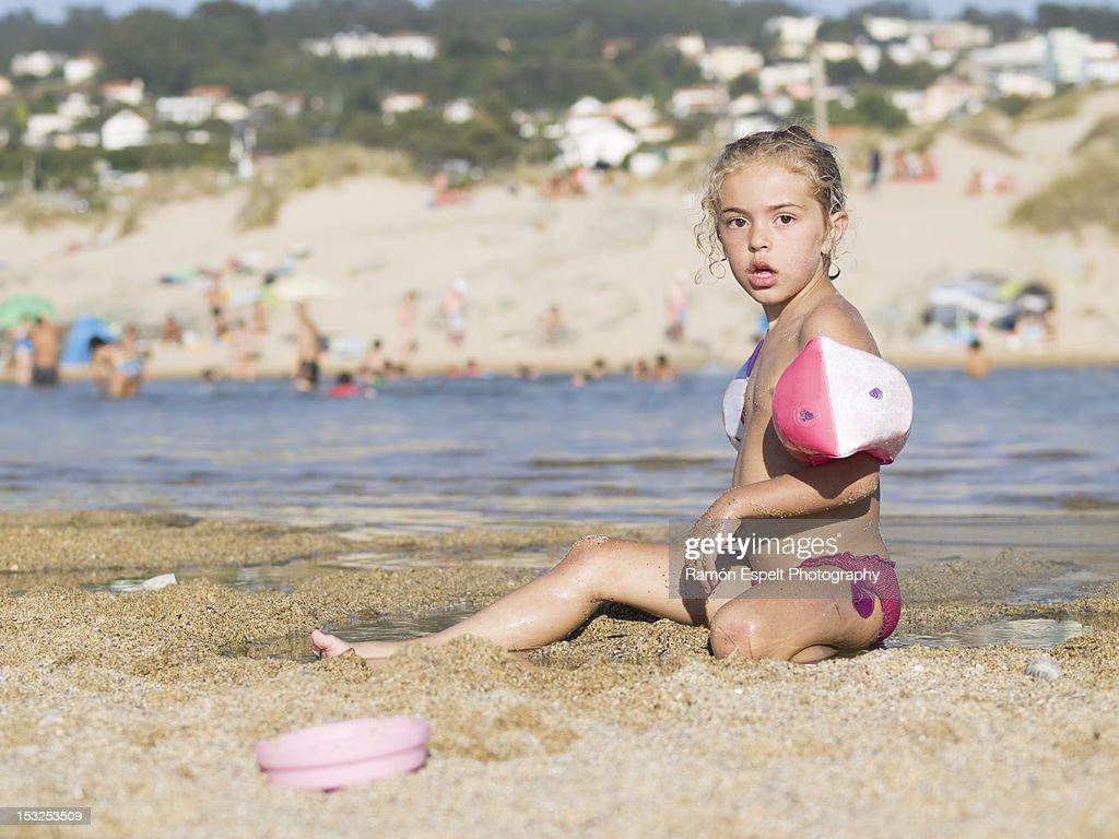 Young Woman Kneeling Amongst Sand Dunes Stock Photo