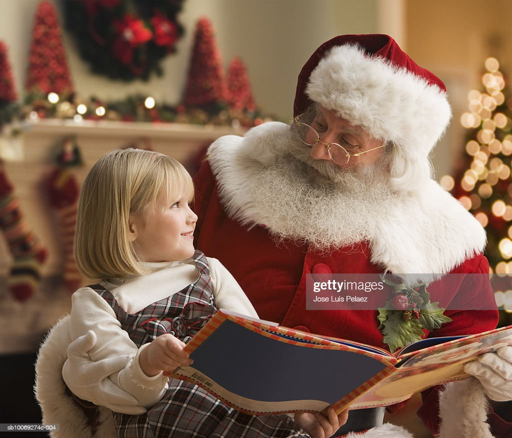 Girl (4-5) sitting on Santa's lap with book, smiling, close-up : Stockfoto
