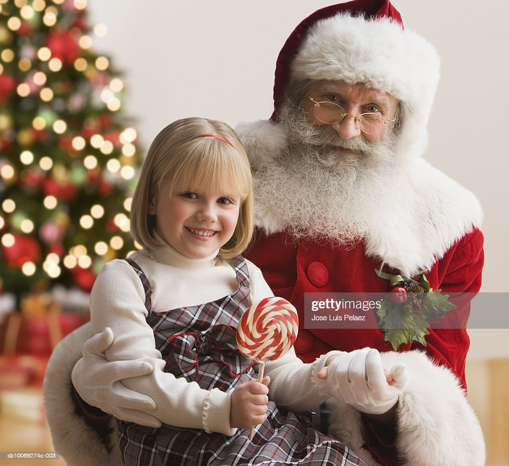 Girl (4-5) sitting on Santa's lap with lollipop, smiling, portrait, close-up : Stockfoto