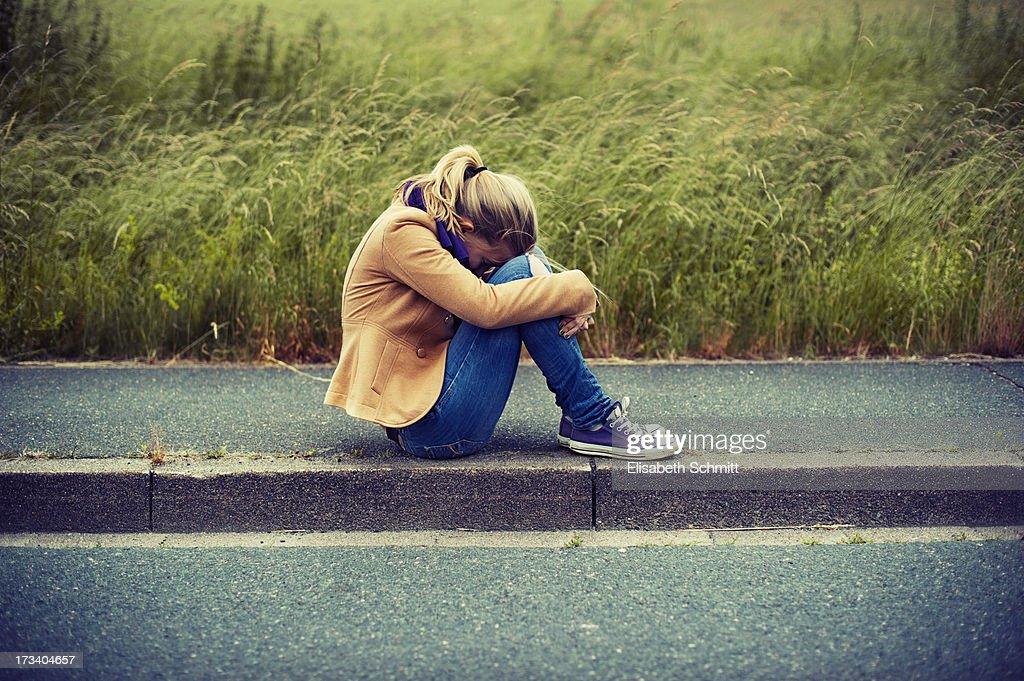Girl sitting on sidewalk, hiding face : Stock Photo