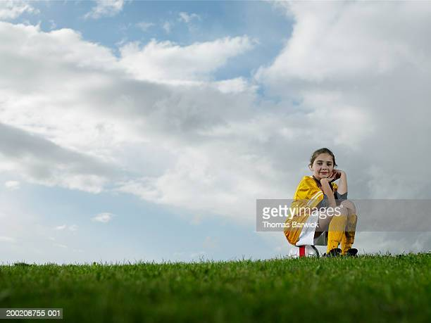 girl (9-11) sitting on soccer ball, resting chin on hand, portrait - pitch stock pictures, royalty-free photos & images