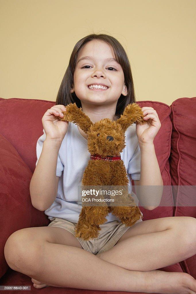 Girl (5-7) sitting on sofa with stuffed animal, portrait : Stock Photo