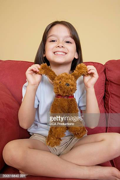 girl (5-7) sitting on sofa with stuffed animal, portrait - dead girl foto e immagini stock